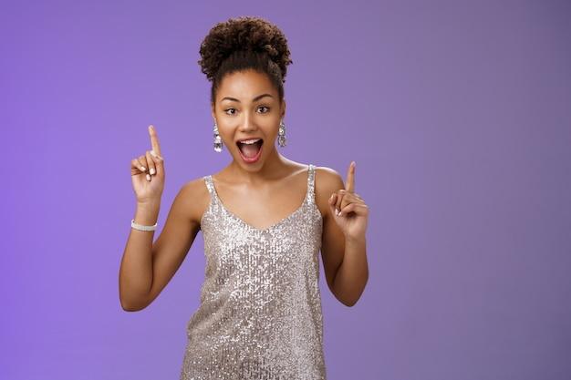 Fortunata bella donna afroamericana che si diverte a ballare celebrando la buona notizia puntando il dito indice verso l'alto stupito sorridendo felice gioendo festa, trionfando ballando vincitore.