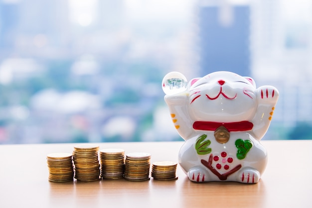 Lucky cat holding glass ball and row of gold coin money on blur background