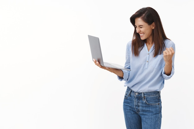Lucky cheerful female entrepreneur receive good news, celebrating, hold laptop rejoice results, fist pump react success, smiling broadly closed eyes, enjoy taste victory, stand white wall