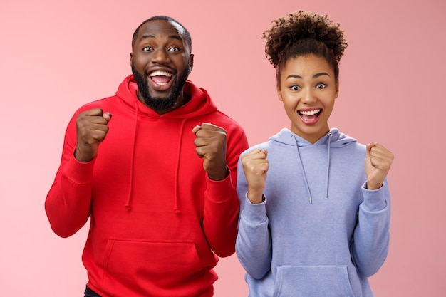 Lucky cheerful two african-american man woman yelling hooray celebrating triumphing huge success clenching fists joyfully accomplish mutual goal standing joyfully pink background victory gesture