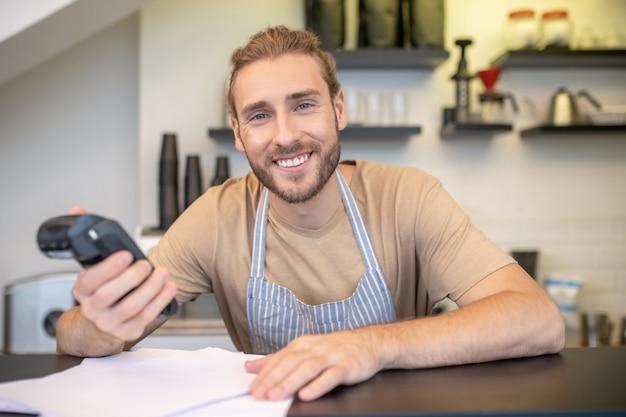 Удачный день. счастливый улыбающийся молодой бородатый мужчина с pos-терминалом в руке у барной стойки, проверяя счета в кафе