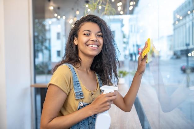 Удачный день. счастливый молодой взрослый длинноволосый мулат женщина, вытирая стеклянную поверхность в кафе салфеткой и спреем