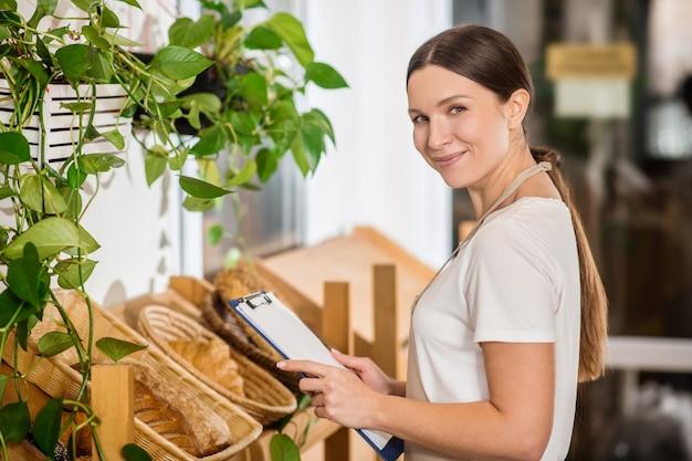 Удачный день. радостная женщина с длинными темными волосами в фартуке с папкой возле стойки хлебобулочных изделий
