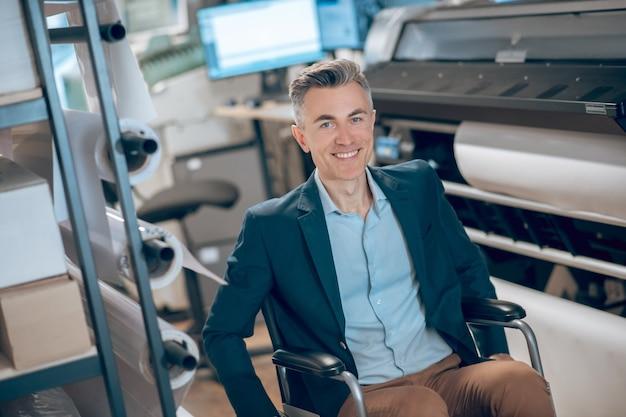 幸運な日。良い気分でコピーセンターで長い紙のロールの近くの車椅子のうれしそうな若い大人の男