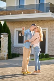 행운의 날. 화창한 날 새 집 근처에 서서 껴안고 웃고 있는 여자와 열쇠를 가진 젊은 성인 행복한 남자