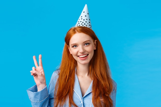 Lucky and enthusiastic feminine pretty redhead woman with long curly hair in nightwear, wearing birthday cap showing peace sign and smiling joyfully, celebrating b-day, blue wall