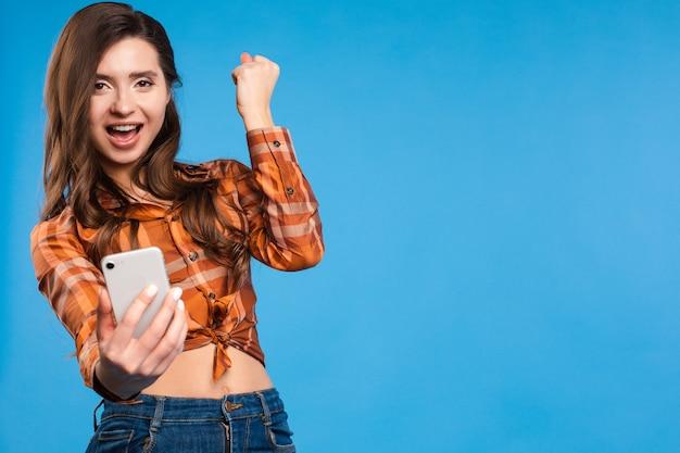 Счастливая девушка в клетчатой рубашке принимает селф и улыбается