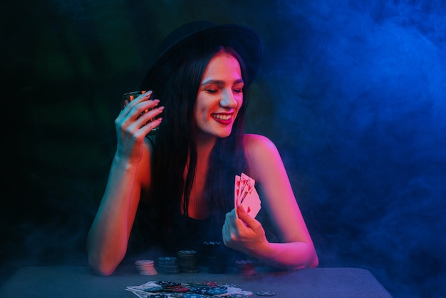 Lucky girl winner plays poker at the table with chips and cards in the casino