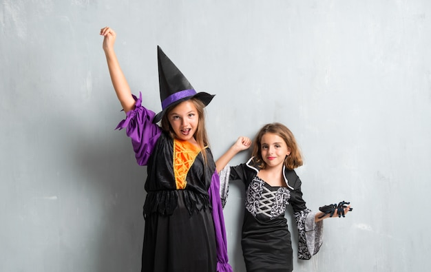 Lucky group of friends with costumes of vampires and witches for halloween holidays