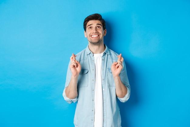 Ragazzo fortunato che prega e esprime desideri con le dita incrociate, alzando lo sguardo con la faccia implorante, in piedi su sfondo blu