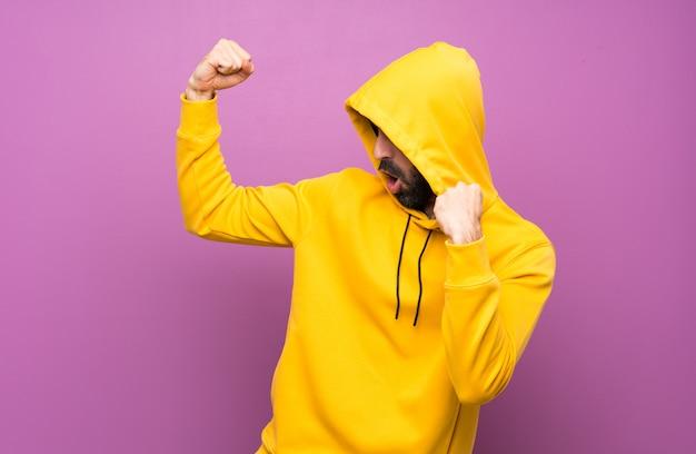 Lucky handsome man with yellow sweatshirt