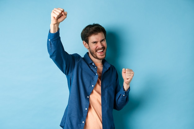 승리를 축하하고 응원하고 기쁨으로 예를 외치는 행운의 남자, 파란색 배경에 서있는 챔피언처럼 손을 들어 올리십시오.