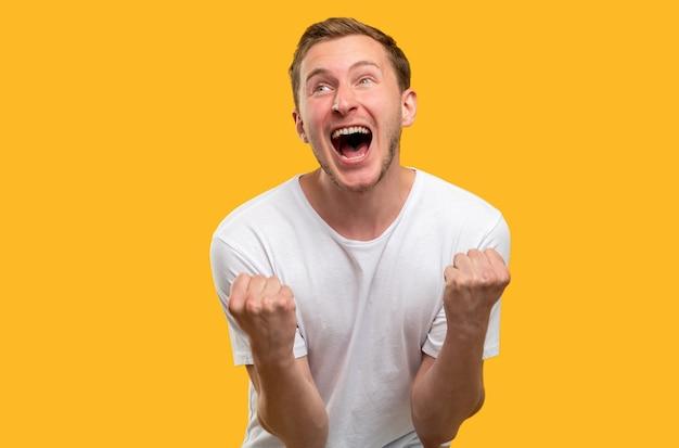 幸運な男の肖像画。勝利のジェスチャー。黄色の背景に分離された勝利の叫びを祝う面白がって男。