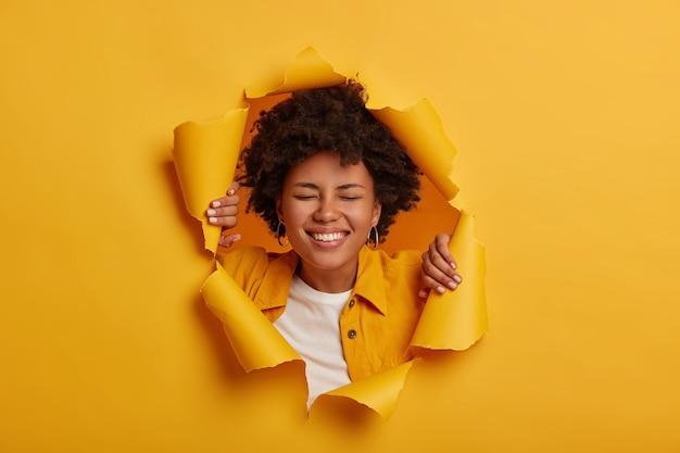 La donna afroamericana felice e felicissima sorride ampiamente, ha uno stato d'animo spensierato, vestita con abiti alla moda si posa sullo sfondo di carta gialla