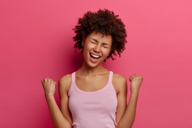 幸運な大喜びの女性の勝者は仕事での勝利を喜ぶ