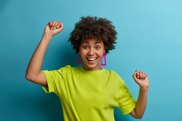 幸運な幸せな巻き毛の若い女性は手を上げて踊り、楽しく、前向きな感情、自由と幸福を表現し、明るい緑色のtシャツを着て、チャンピオンのように感じ、目標を達成しました