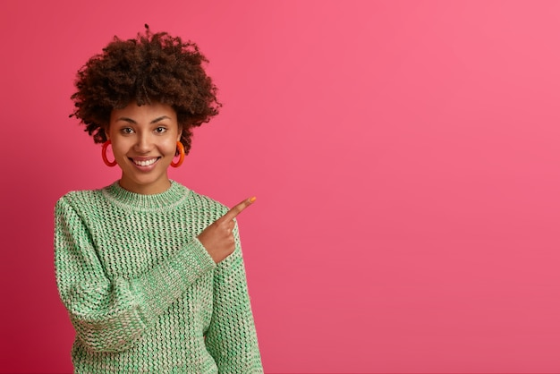 Lucky pleased dark skinned woman points with happy expression, shows copy space for your advertisement, recommends visit shopping site, click link, wears knitted sweater over rosy  wall