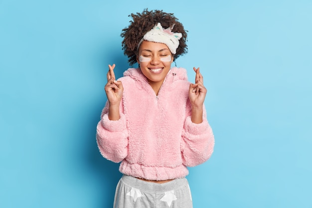 巻き毛の幸運なポジティブな女性が指を交差させる夢が叶うと信じているパジャマを目隠しするコラーゲンパッチを適用してしわを減らし、睡眠の準備をする