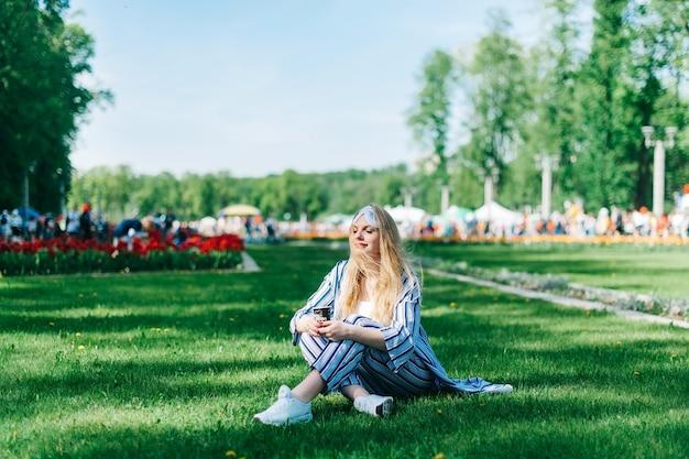 幸運なきれいな女性はパジャマと睡眠マスクの緑の草の上に座って、太陽を楽しみ、コーヒーを飲む