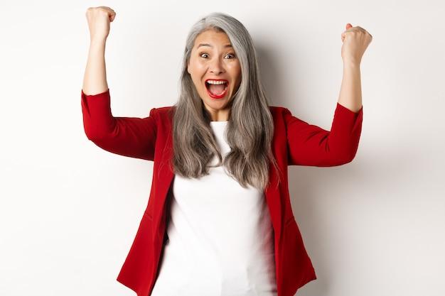 幸運な年配の女性は成功を収め、賞を獲得し、白い背景に対して幸せに立って、拳ポンプで「はい」と言って祝います。