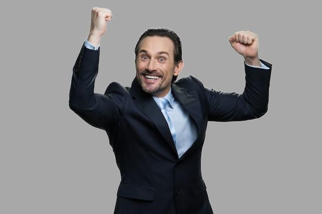 幸運な成功した実業家は彼の拳を食いしばった。勝利を祝うビジネススーツの感情的な白人男性。ラッキーウィナーコンセプト。