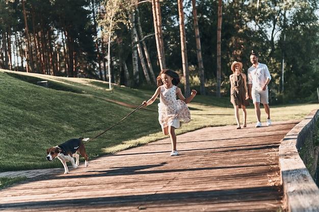 함께할 수 있어 행운입니다. 그녀의 부모가 뒤에 걷는 동안 강아지와 함께 달리고 웃는 귀여운 소녀의 전체 길이