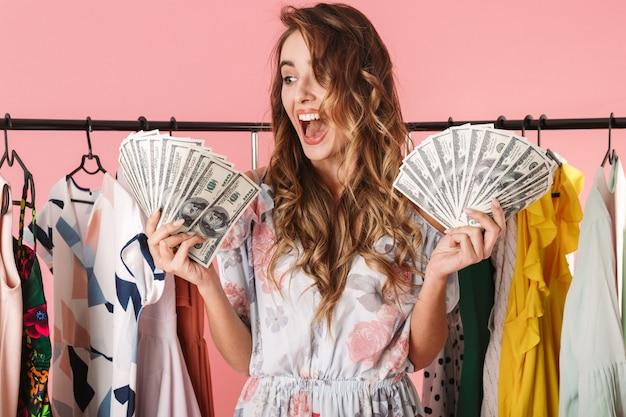 Счастливая женщина, стоящая возле шкафа, держа в руках денежные вентиляторы, изолированные на розовом