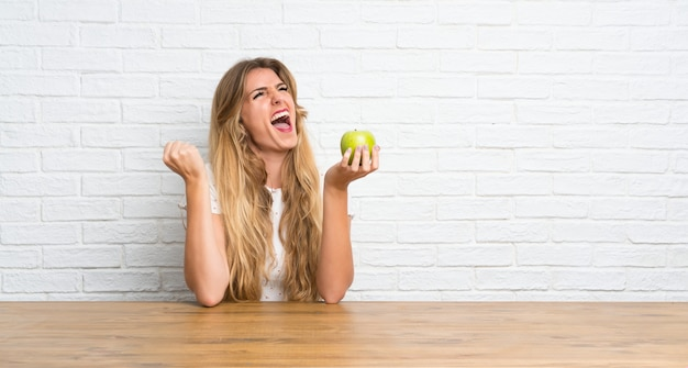 Lucky young blonde woman with an apple