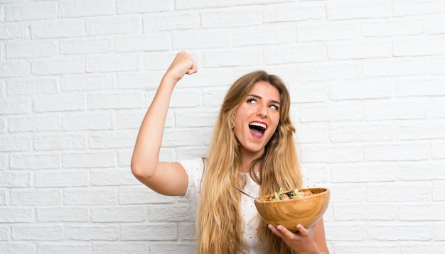Lucky young blonde woman with salad