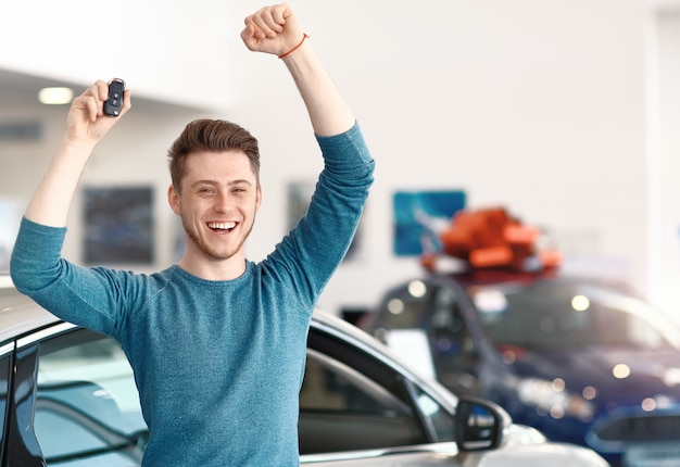 Lucky young male winner in car dealership