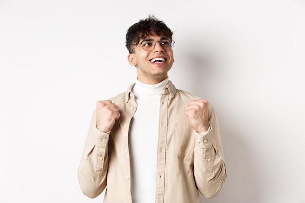 幸運な若い男は、ほっとした顔で、笑顔で拳ポンプを作り、成功の勝利、賞を獲得し、目標を達成した後、白い背景の上に立って「はい」と言います 無料写真