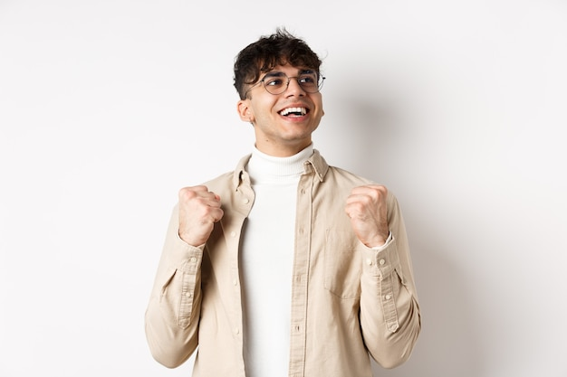 Lucky young man say yes with relieved face, smiling and making fist pump, triumphing of success, winning prize, standing on white wall after achieving goal.