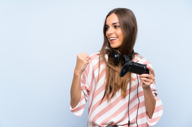 Lucky young woman playing with a video game controller over isolated blue wall