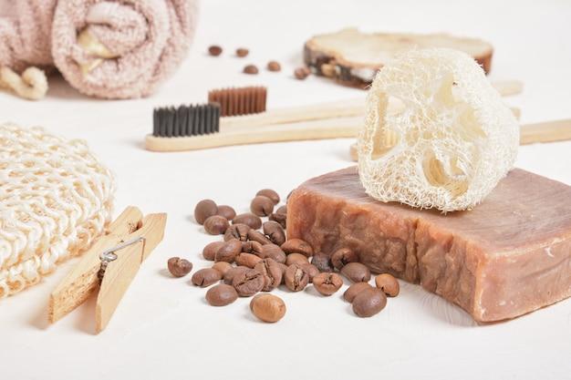 Домашнее мыло из люффы и какао, бамбуковые зубные щетки и аксессуары для ванной из натуральных материалов, кофейных зерен, бежевая поверхность.