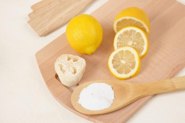Люффа, лимон и пищевая сода на деревянной ложке, вязальная доска на бежевом фоне, копия пространства, концепция эко-очистки