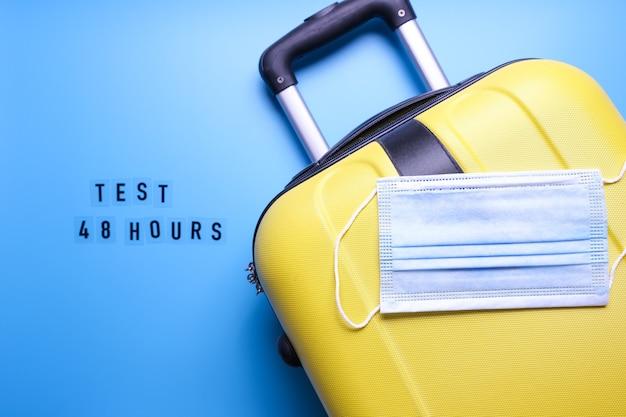 青い背景の荷物バッグとマスク。 covid48時間のワードテスト。 covidテストでのみ旅行してください。