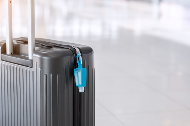 Luggage bag with alcohol gel hand sanitizer in international airport terminal, protection coronavirus disease (covid-19) infection. new normal and travel bubble concepts