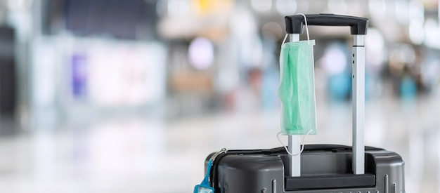 Luggage bag with surgical face mask and alcohol gel hand sanitizer in international airport terminal, protection coronavirus disease (covid-19) infection. new normal and travel bubble concepts