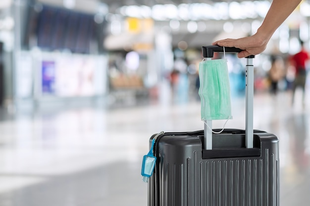 Luggage bag with surgical face mask and alcohol gel sanitizer in airport