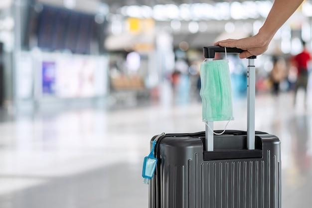 Сумка для багажа с хирургической маской для лица и дезинфицирующим средством на спиртовом геле в аэропорту