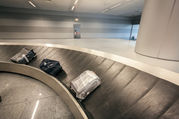 Luggage claim carousel with three bags at airport terminal