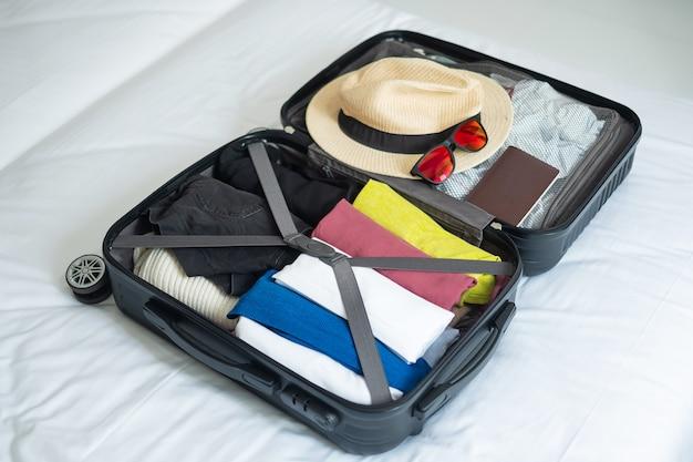 Камера для летнего отдыха. дорожные аксессуары в чемодане на кровати. концепции времени для путешествий, отдыха, путешествий, поездок и выходных