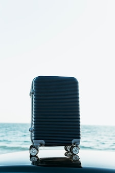 Luggage sitting on top of car near sea