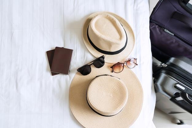 Багаж, соломенная шляпа, солнцезащитные очки и паспорт пары на кровати. приготовьтесь к путешествию, концепция праздника.