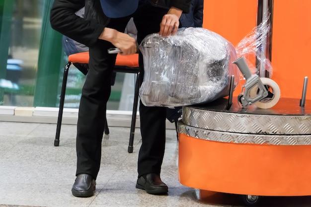 セキュリティ上の理由と損傷からの安全保護のための空港ターミナルでの荷物ラッピングサービス。飛行機で旅行する前に荷物を包む。