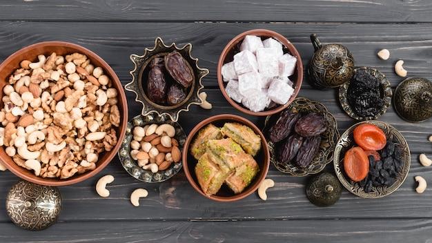 Лукум; даты; сухофрукты; пахлава и орехи на глиняной и металлической миске на деревянном столе