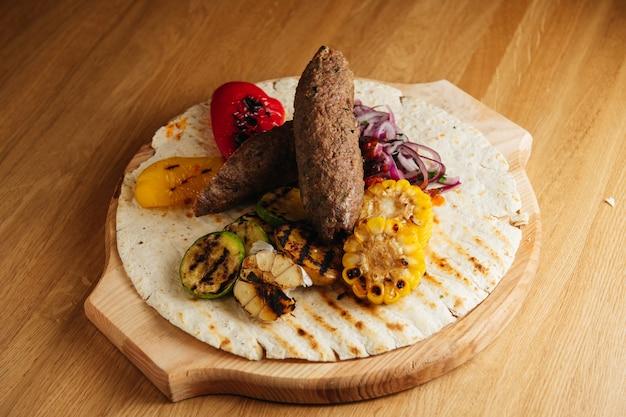 Люля-кебаб из баранины с овощами гриль. подается на деревянном подносе