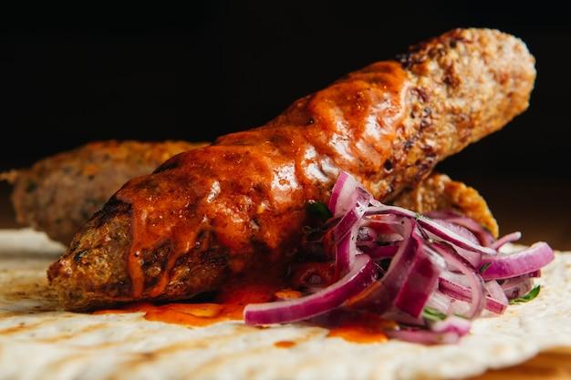 Люля кебаб с лавашем, соусом и луком на деревянной доске