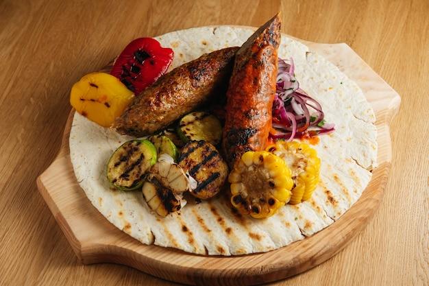 Люля кебаб с лавашем, соусом, кукурузой на гриле и луком на деревянной доске