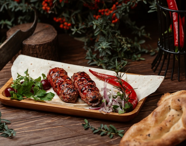 Lule kebab in barbecue sauce with red hot pepper